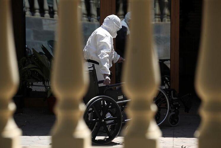 Un travailleur introduit un fauteuil roulant dans une résidence à San ...