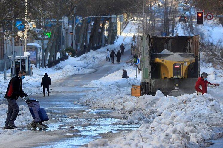 Plusieurs personnes marchent dans une rue de Madrid avec un chasse-neige ...