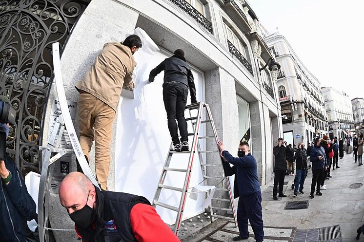Plusieurs ouvriers réparent une vitrine dans la Puerta ...