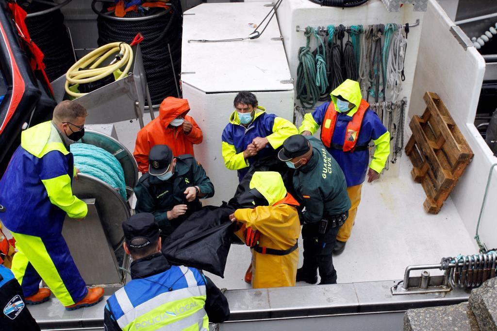 Des agents de la Garde civile et des marins déplacent le corps d'un des défunts.