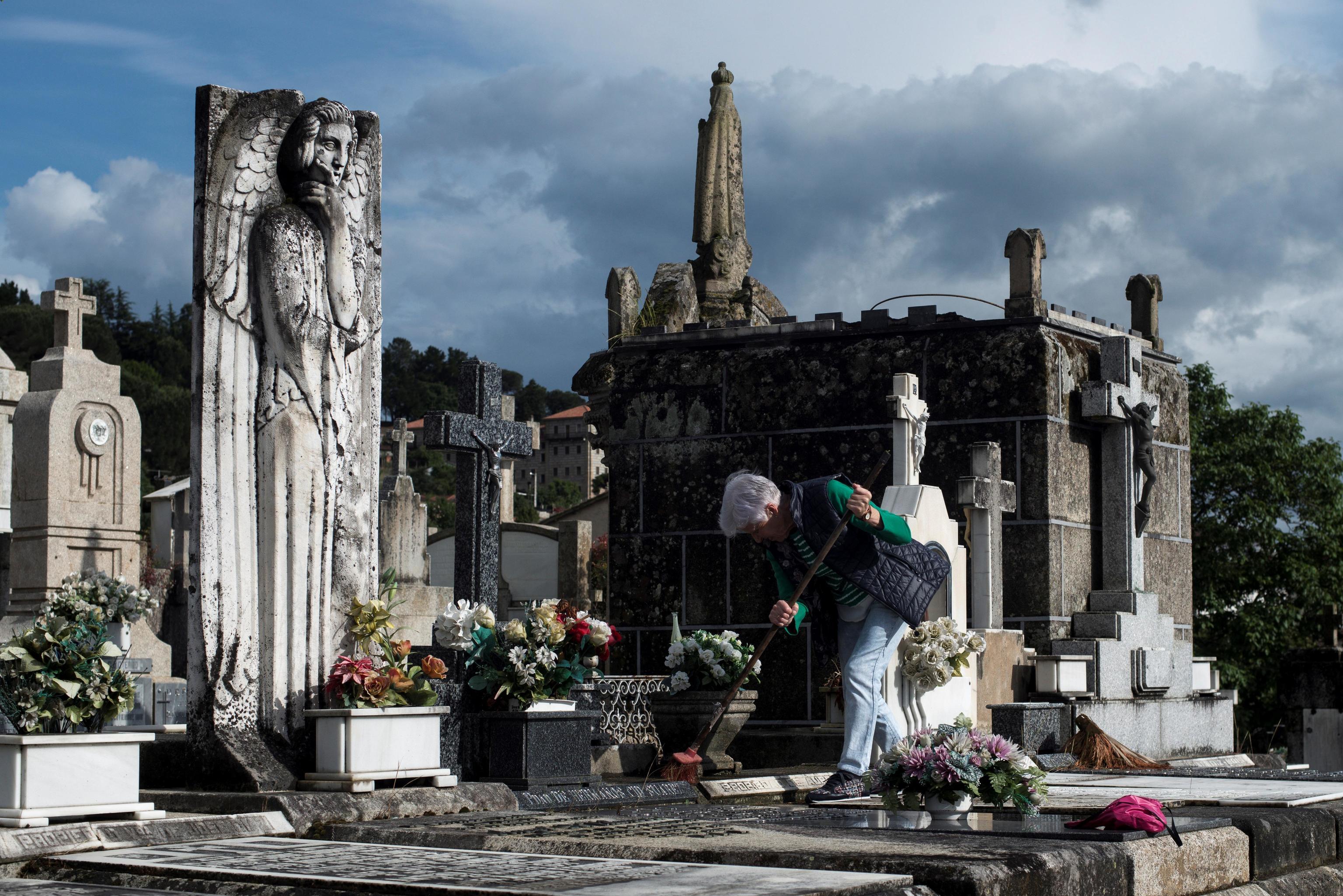 Une femme effectue des travaux de nettoyage dans le cimetière de San Francisco à Ourense.