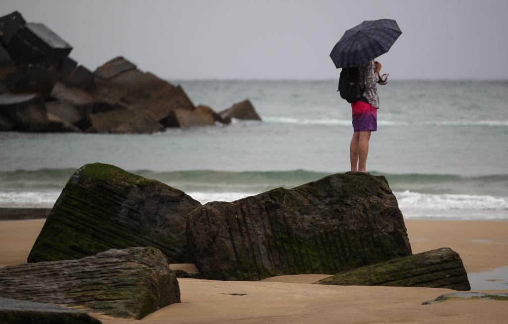 Un jeune homme se protège avec un parapluie sur la plage de Zurriola à San Sebasti