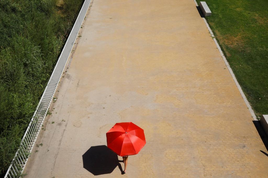 Une jeune fille se protège du soleil sous un parapluie en C